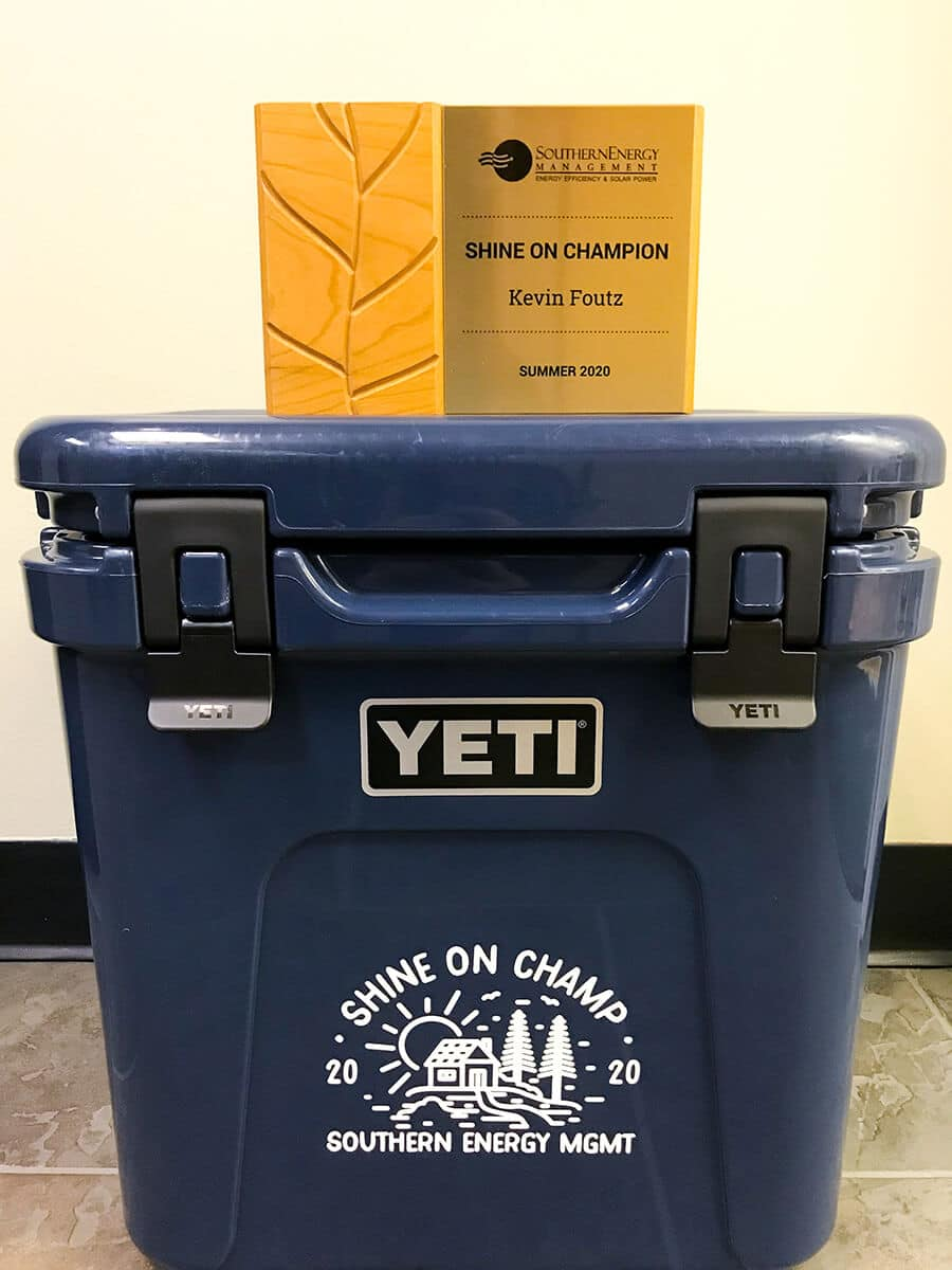 Navy blue Yeti Cooler branded with the Shine On Champion emblem and an award plaque sitting on top.