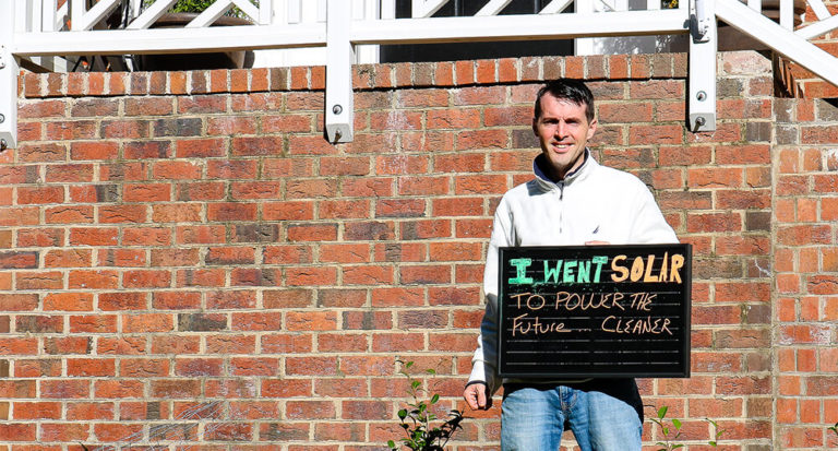 """Solar customer holding sign saying """"I went solar to power the future... cleaner"""""""