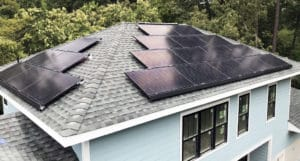 New construction blue house with rooftop solar panels
