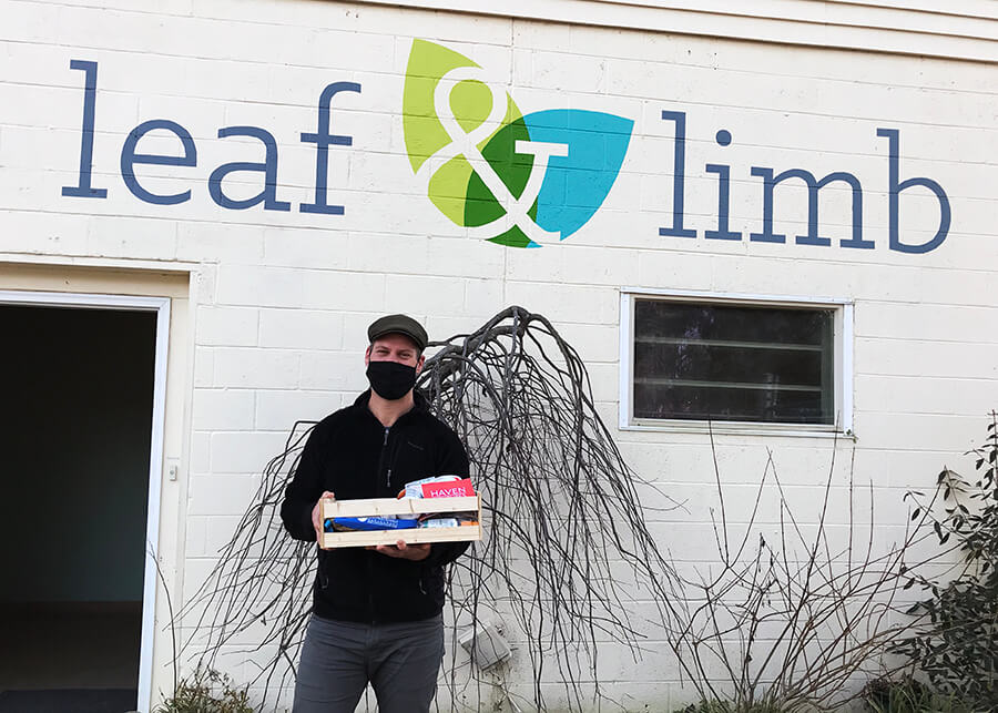 Basil, Co Founder of Leaf & Limb, holding welcome gift from NC B Corps in front of Leaf & Limb's office