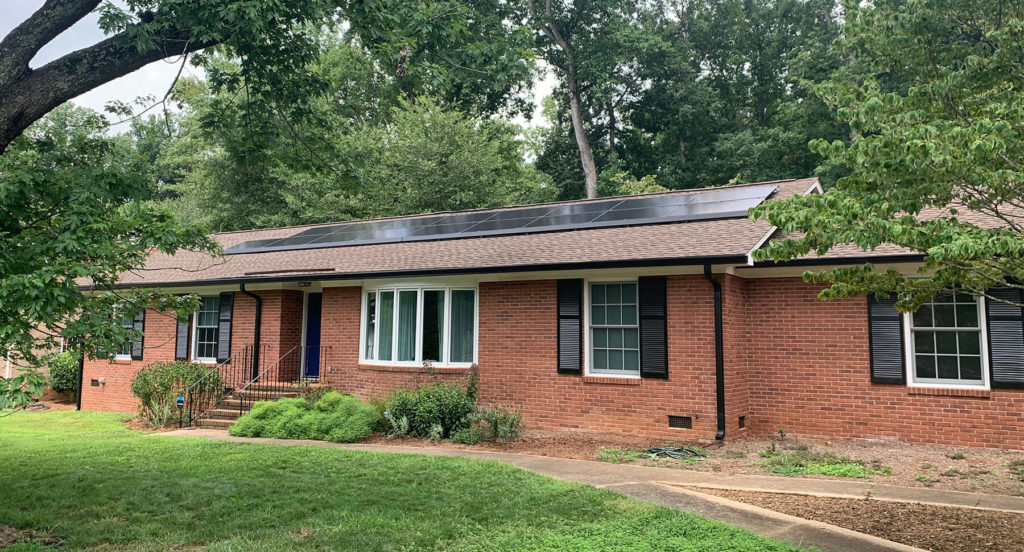 Brick one story home with solar panels on the front roof