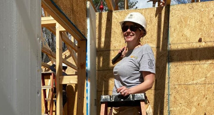 Kelley on a ladder at a construction site during a Habitat Home build