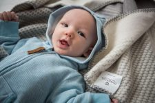 Baby snuggled in a grey patterned nurturing serenity blanket from Thread Talk