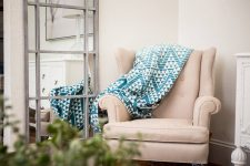 Blue triangle pattered Strength blanket from Thread Talk draped over a cream arm chair
