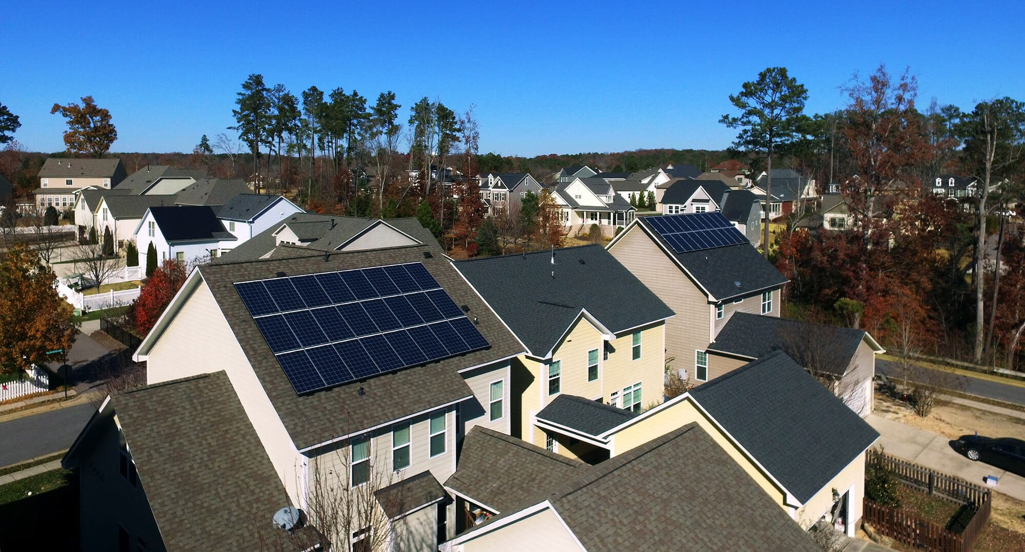 Two neighboring homes with rooftop solar systems on the same street