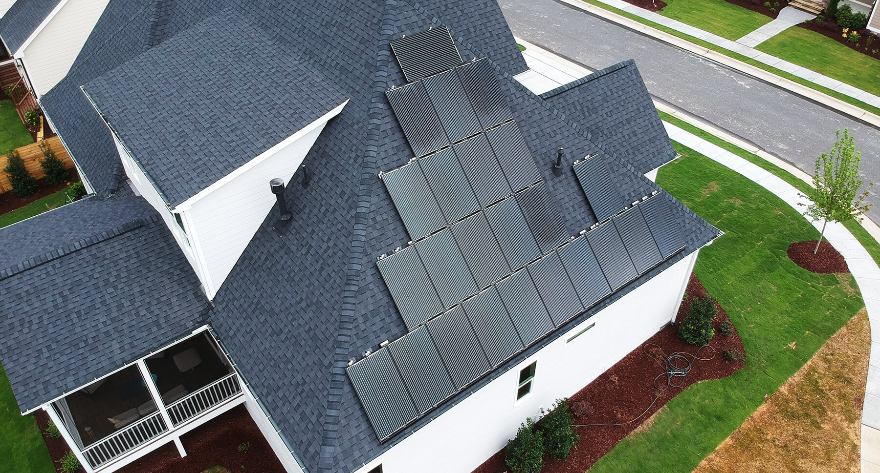 Aerial view of a home with black solar panels on the roof