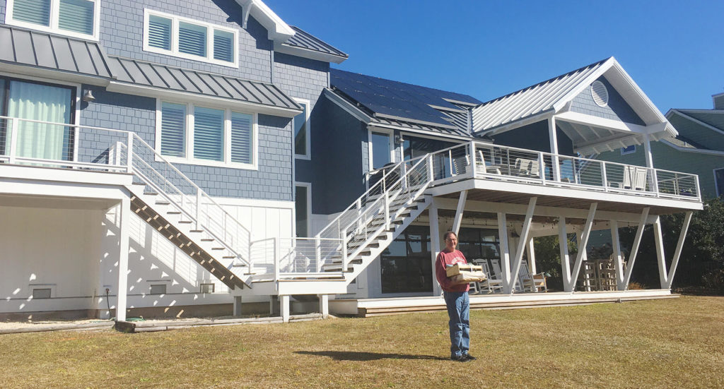 Solar referral basket winner from Southern Energy Management standing in front of his home solar system