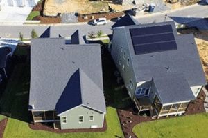 New construction home with solar next to a home without solar on the roof