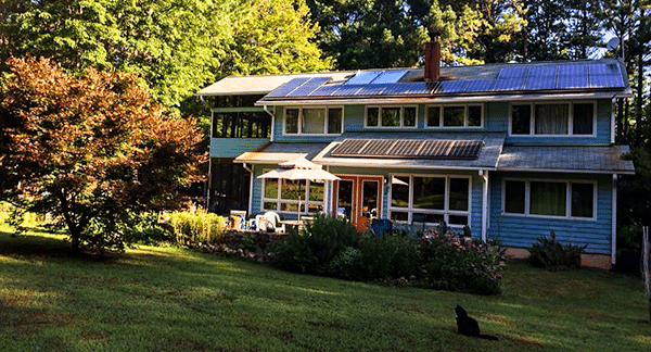 Home with a rooftop solar system and a black cat in the yard